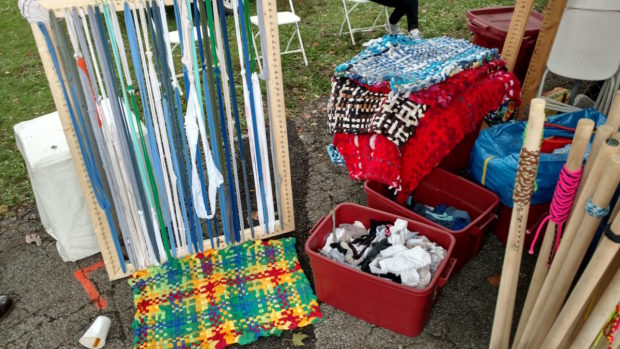 Attendees get the opportunity to weave their own giant potholders from upcycled wool and cotton at the GreenSheeep tent. (1:24pm, Sophia Smith)